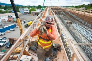 Rebar placed at Tillamook Structure, East Segment: A crew member carries rebar on top of the under construction Tillamook structure in north Milwaukie. Spring 2013