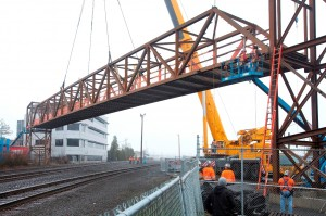 A 70-ton, 184-foot pedestrian/bike span is lifted into place over the Union Pacific Railroad tracks.
