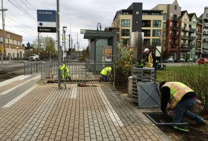 Crews work at the Civic Dr MAX Station, laying the conduit for e-fare card readers that will be installed in the future.